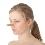 Disgusted woman with clothespin clipped to nose